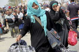 Displaced Sunni women fleeing the violence in Ramadi, carry bags as they walk on the outskirts of Baghdad, May 24, 2015.