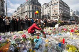 A woman lays flowers on a memorial to victims of the Brussels attacks during a march against hate in Brussels on Sunday, April 17, 2016.