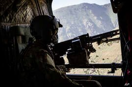 A photo released by Operation Resolite Support shows a US Army CH-47 Chinook helicopter crew scanning below near Mazar-e-Sharif, Afghanistan, June 9, 2017.