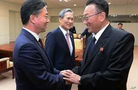In this photo provided by the South Korean Unification Ministry, Unification Minister Hong Yong-pyo, left, shakes hands with Kim Yang Gon, a senior North Korean official responsible for South Korean affairs, after their meeting at Panmunjom in Paju, ...