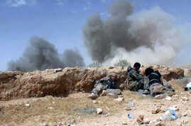 In this picture released on Wednesday, May 20, 2015 by the website of Islamic State militants, Islamic State fighters take cover during a battle against Syrian government forces on a road between Homs and Palmyra, Syria.