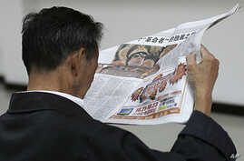 A man reads a local newspaper's story on the spread pages featuring a photo of Moammar Gadhafi at a private securities company in Shanghai, China, Oct. 21, 2011.