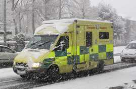 FILE - An Emergency Ambulance drives through a snow storm in Ealing, London.