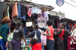 Women look at second hand clothes at roadside stall, in Nairobi, Kenya, April 8, 2018.