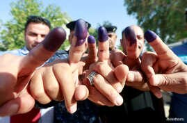Iraqi security members show their ink-stained fingers after casting their vote at a polling station two days before polls open to the public in a parliamentary election, in Najaf, Iraq, May 10, 2018.