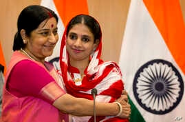 India's External Affairs Minister Sushma Swaraj, left, hugs Geeta, 23, a deaf and mute Indian woman who accidentally strayed into Pakistan as a child 12 years ago, during a press conference in New Delhi, India, Oct. 26, 2015.