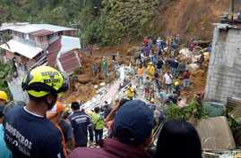 In this handout photo released by the Caldas Department Press Office, rescue workers attend to the wreckage of a house destroyed by a landslide in Marquetalia, Colombia, Oct. 11, 2018.