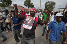 A demonstrator dances as he carries a picture of Haiti's former President Jean-Bertrand Aristide during a march against President Michel Martelly's government in Port-au-Prince, Haiti, Monday, Sept. 30, 2013. Critics of Martelly marched through the c
