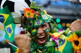 A Brazil soccer fan covered in flowers and his nation's flag cheers inside the FIFA Fan fest area before the start of the World Cup openes between Brazil and Croatia on Copacabana beach, Rio de Janeiro, Brazil, June 12, 2014.