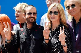 Ringo Starr, left, poses with his wife Barbara Bach, center, and guitarist Joe Walsh, right, during a 77th birthday celebration for Starr at Capitol Records, July 7, 2017, in Los Angeles.