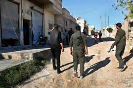 Members of the Kurdish internal security forces pass damaged shops in the area where an explosion hit U.S.-led coalition vehicles, killing an American and a Briton soldiers, in Manbij, Syria,  March 31, 2018.