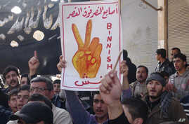 "This citizen journalism image provided by Edlib News Network (ENN), shows an anti-Syrian regime protester holding up an Arabic placard reading: ""the victory fingers over the [presidential] palace,"" during a demonstration, at Binnish village, in Idlib"