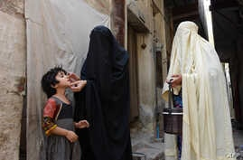 A Pakistani health worker administers the polio vaccine to a child during a vaccination campaign in Bannu on June 25, 2014.