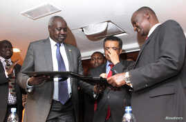South Sudan's leader of the government's delegation Nhial Deng Nhial (L) exchanges a signed ceasefire agreement with the head of the rebel delegation Gen. Taban Deng Gai (R) to end more than five weeks of fighting after negotiations in Ethiopia's cap