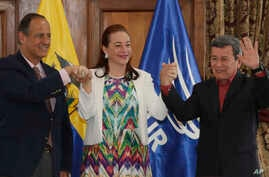 Ecuador's Foreign Minister Fernanda Espinosa stands between ELN rebel leader Pablo Beltran, right, and Colombia's government representative Juan Camilo Restrepo at the end of a press conference announcing the signing of a cease-fire in Quito, Ecuador