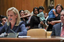 FILE - Women carrying children in their arms stand up to protest Homeland Security Secretary Kirstjen Nielsen, left, during Nielsen's opening remarks before Senate Appropriations subcommittee hearing on Capitol Hill in Washington, May 8, 2018.