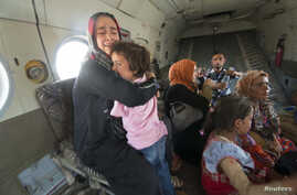 A woman holding a child reacts in a military helicopter after being evacuated by Iraqi forces from Amerli, north of Baghdad August 29, 2014.