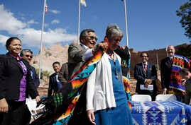 Navajo Nation President Ben Shelly (L) puts a blanket on the shoulders of U.S. Interior Secretary Sally Jewell after a ceremonial signing of a record multi-million-dollar settlement, in Window Rock, Arizona, at the Navajo Nation, Sept. 26, 2014.