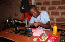 Girls at the Parents Care Infant Academy, including 14-year-old Catherine Nantume, are sewing a reusable sanitary towel in Makindye Kampala.