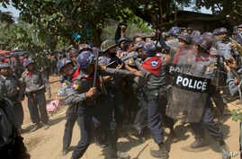 Police officers beat a student protester after detaining him following a crackdown in Letpadan, 140 kilometers (90 miles) north of the country's main city Yangon, Myanmar, Tuesday, March 10, 2015. Hundreds of police were charging student protesters w