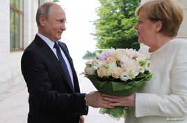 Russian President Vladimir Putin welcomes German Chancellor Angela Merkel during their meeting in the Black Sea resort of Sochi, Russia, May 18, 2018.