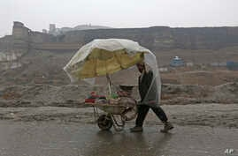 FILE - A vendor pushes his makeshift cart under a plastic cover in the rain, on the outskirts of Kabul, Afghanistan, Jan. 30, 2017.