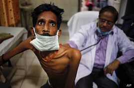FILE - A doctor examines a tuberculosis patient in a government TB hospital in Allahabad, India, March 24, 2014. A new treatment regimen for the disease costs less than $1,000 per patient and can be completed between nine and 12 months.