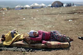 A Syrian girl who fled with her family from the violence in their village, rests at a displaced camp, in the Syrian village of Atmeh, near the Turkish border, Nov. 5, 2012.