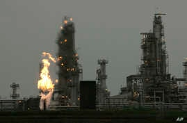 FILE - A Tesoro Corp. refinery, including a gas flare flame that is part of normal plant operations, is shown in Anacortes, Wash., after a fatal overnight fire and explosion, April 2, 2010. Voters in Washington state rejected Initiative 732 in the 20