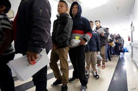 A line of migrants recently released by U.S. immigration authorities waits to check in at the Catholic Charities shelter in McAllen, Texas, Jan. 11, 2019.