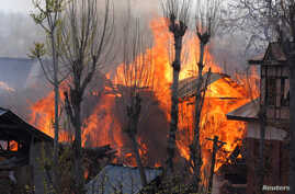 Flames and smoke billow from residential houses after they caught fire during a gunbattle between Indian army soldiers and suspected militants at Kachdoora village in south Kashmir's Shopian district, Apr. 1, 2018.