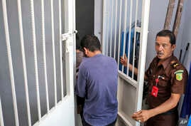 A security official from the prosecutor's office escorts two men accused of having gay sex into a holding cell to wait for the start of their trial at Sharia court in Banda Aceh, Indonesia, May 10, 2017.