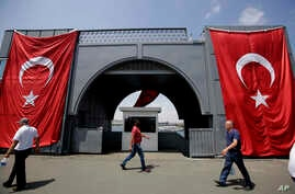 Men walk at the Galata bridge past two Turkey flags, in Istanbul, on Tuesday, Aug. 2, 2016.