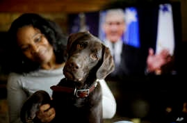 "Alicia Barnett sits with her Chocolate Labrador Retriever named ""Mueller"" in their Kansas City, Kan., home on March 11, 2019."