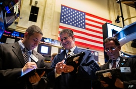 Traders work on the floor of the New York Stock Exchange shortly after the opening bell in the Manhattan borough of New York, April 2, 2014.