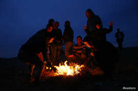 Turkish Kurds sit around a fire to warm themselves as they watch the Syrian town of Kobani from a hill near the Mursitpinar border crossing, on the Turkish-Syrian border in the southeastern town of Suruc, Turkey, Oct. 22, 2014.