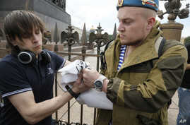 FILE - A former paratrooper celebrating Paratroopers Day, right, takes away a broadsheet of a gay rights activist who is taking part in a protest at Dvortsovaya (Palace) Square in St. Petersburg, Russia, Aug. 2, 2015.