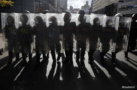 National Guards walk with their shields up as they keep guard during a street protest in support of jailed opposition leader Leopoldo Lopez in Caracas, Feb. 18, 2015.