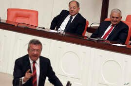 Prime Minister Binali Yildirim, rear right, smiles as he listens to opposition lawmaker Engin Altay before a parliamentary vote in Ankara, Turkey, Sept. 23, 2017. The Turkish parliament renewed a bill allowing the military to intervene in Iraq and Sy