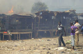 Men stand and watch as a fire rages in the background during clashes between rival gangs in Marche Madina, in Conakry Mar. 1, 2013