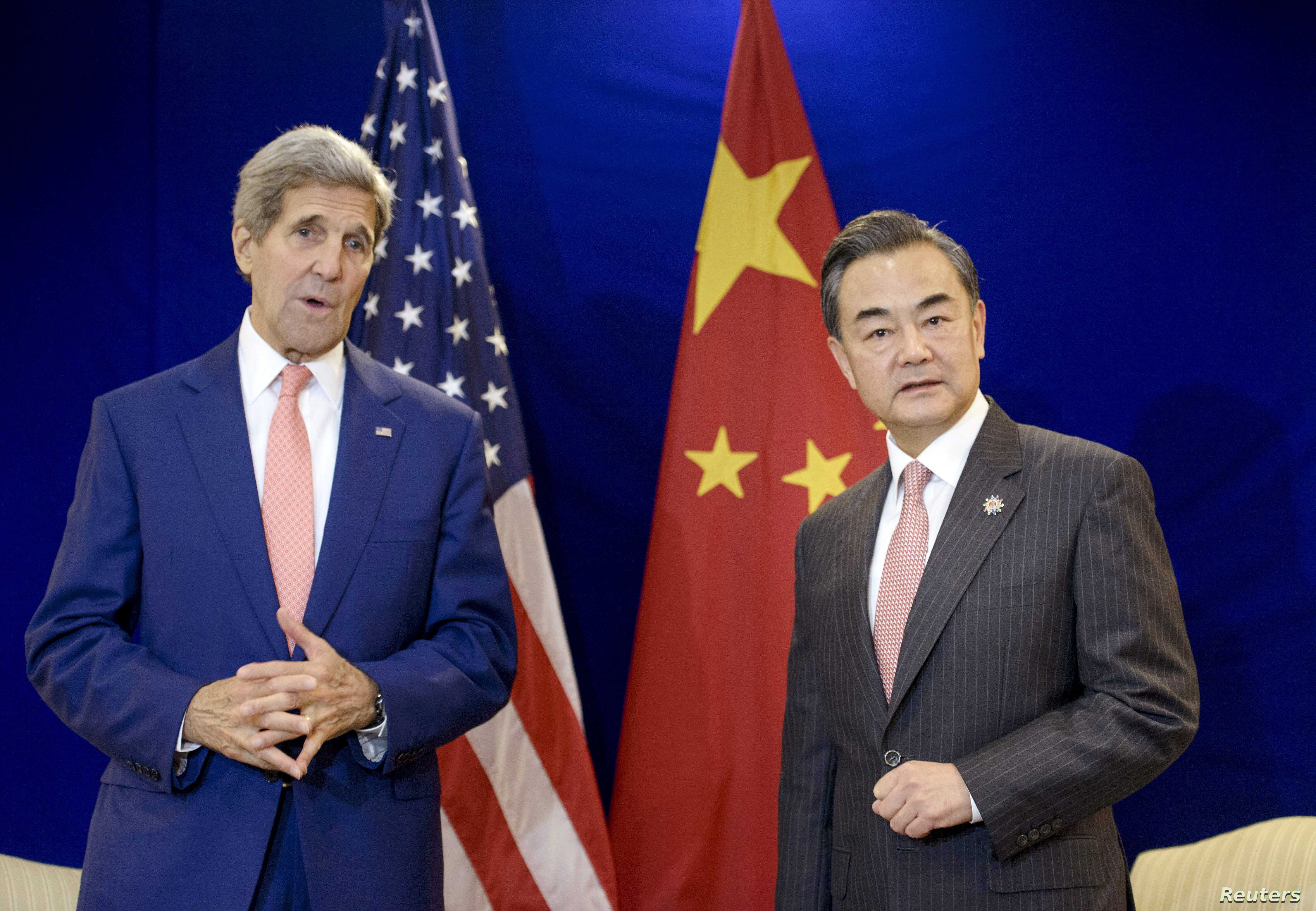 China's Foreign Minister Wang Yi (R) listens while US Secretary of State John Kerry talks before a bilateral meeting at the Putra World Trade Center Aug. 5, 2015 in Kuala Lumpur, Malaysia.
