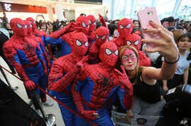 """Event workers wearing Spider-Man costumes pose for a selfie for a fan during a promotional event for the film """"Spider-Man: Homecoming"""" in Seoul, South Korea, Sunday, July 2, 2017."""