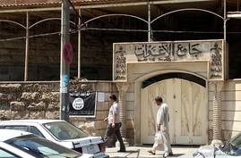 FILE - People walk past a banner of the Islamic State in Iraq and the Levant (ISIL) in the city of Mosul, June 28, 2014.