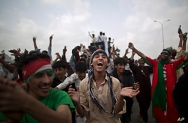 Supporters of Pakistan's cricketer-turned-politician Imran Khan, chant slogans, while waiting for other supporters marching to Islamabad from Lahore, in Islamabad, Pakistan, Friday, Aug. 15, 2014.