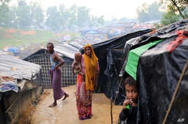 A Rohingya woman holds her child and stands at a makeshift camp near Kutupalong refugee camp in Cox's Bazar, Bangladesh, Oct. 3, 2017. More than half a million Rohingya have fled from Myanmar to Bangladesh in just over a month, the largest refugee cr...