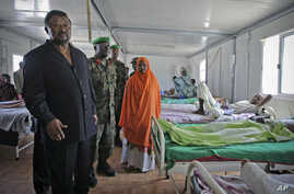 Jean Ping (L), chairman of the Commission of the African Union, visits wounded Transitional Federal Government soldiers at the African Union Mission in Somalia Level II hospital, at the operation's headquarters in Mogadishu, Somalia, August 20, 2011.