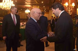 Afghanistan's deputy foreign minister, Hekmat Khalil Karzai, right, and Pakistani foreign affairs adviser Sartaj Aziz exchange greetings before a four-nation meeting to develop a peace process for Afghanistan. Richard Olson, U.S. special representa...