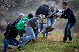 Palestinians carry an injured man during clashes with Israeli soldiers outside the Ofer military prison near the West Bank city of Ramallah, Jan. 2, 2015.