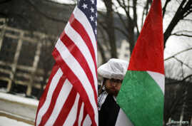 FILE - A demonstrator with U.S. and Palestinian flags protests silently outside the American Israel Public Affairs Committee policy conference in Washington, March 1, 2015.
