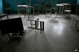 Desks and chairs sit in an abandoned classroom at a public high school in Caracas, Venezuela. Officially, Venezuela canceled 16 school days this year, including Friday classes because of an energy crisis, June 1, 2016.